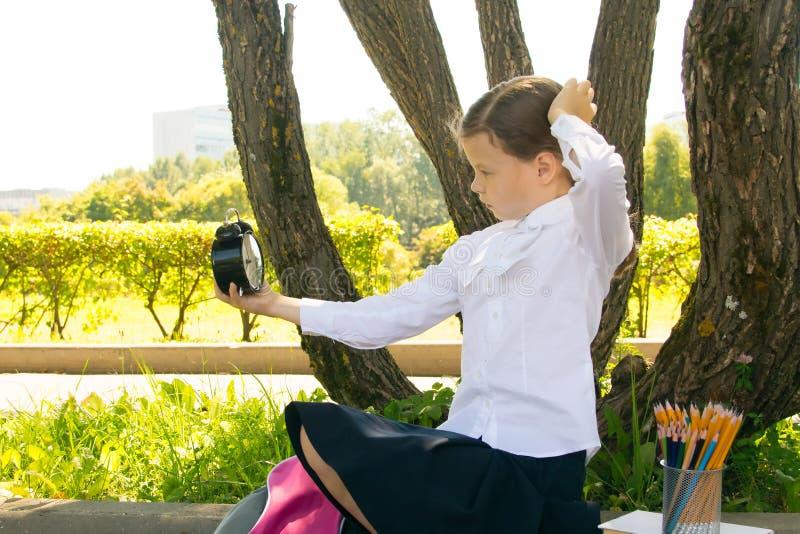 Im Park in der Frischluft, dachte ein Schulmädchen und hielt einen Wecker in ihren Händen, an Zeit stockfotografie