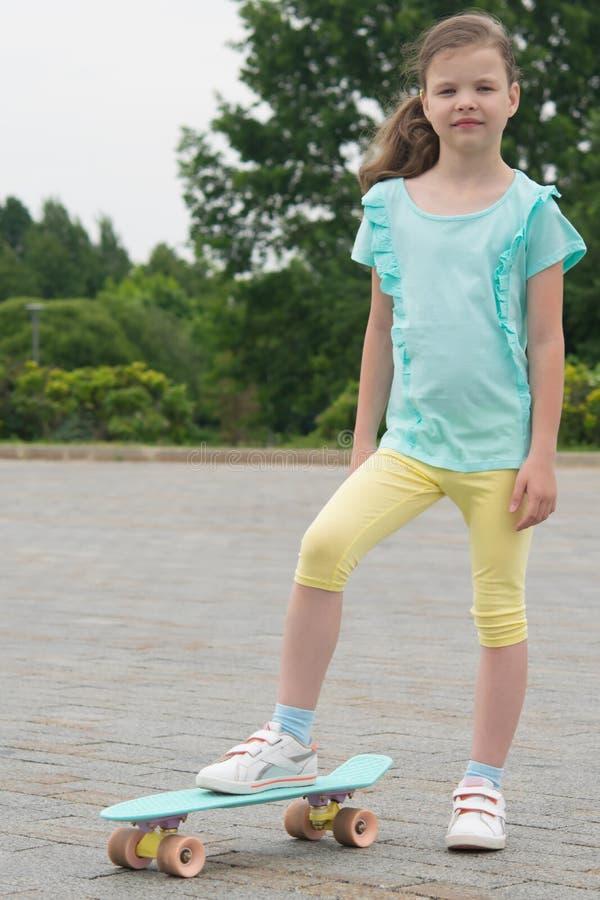 Im Park in der Frischluft, gibt es ein Mädchen auf einem Skateboard, auf einem Steinblock lizenzfreie stockbilder