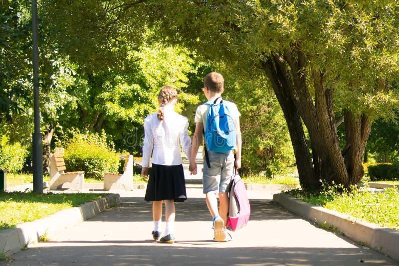 Im Park in der Frischluft, halten Schulkinder Hände, die hintere Ansicht, der Junge trägt Mädchen eines Rucksacks lizenzfreie stockbilder