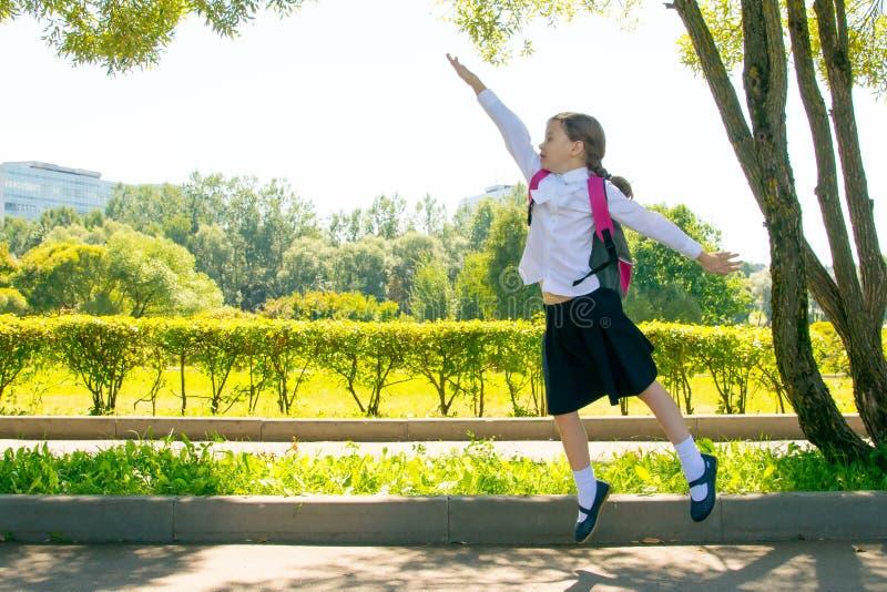 Im Park in der Frischluft, hat ein Schulmädchen Spaß und springt oben und hebt ihre Hand an stockfoto