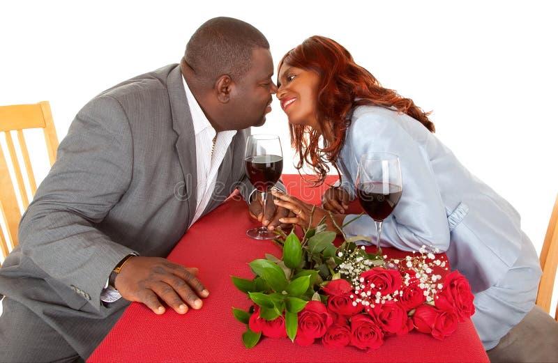 Im romantischen Abendessen zu küssen Afroamerikaner-Paare ungefähr, stockbild