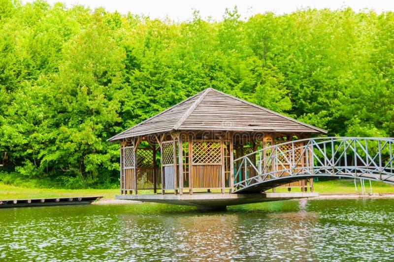 Im Sommer auf dem See Holzhaus auf dem Ufer des Teichs Reflexion von Wolken des blauen Himmels im Wasser stockbilder