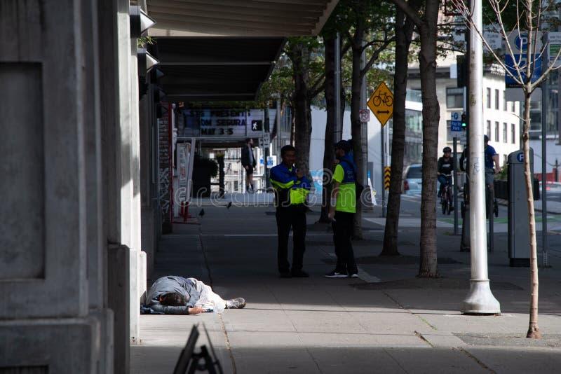 Im Stadtzentrum gelegene Botschafter Seattles auf Bürgersteig nahe bei obdachlosem Mann stockbild