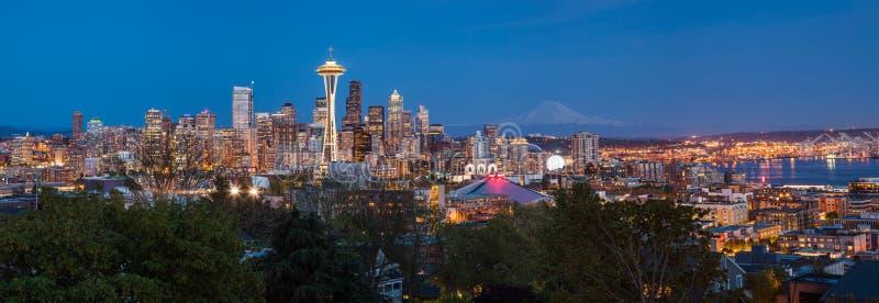 Im Stadtzentrum gelegene Skyline Seattles und Mt Regnerischer nachts lizenzfreie stockfotos