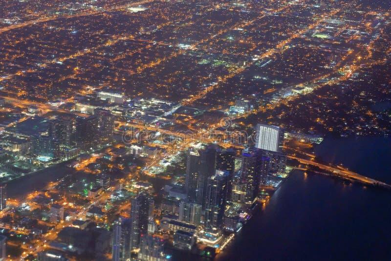 Im Stadtzentrum gelegenes Miami beleuchtet nachts von Abreiseflugzeugen stockbilder