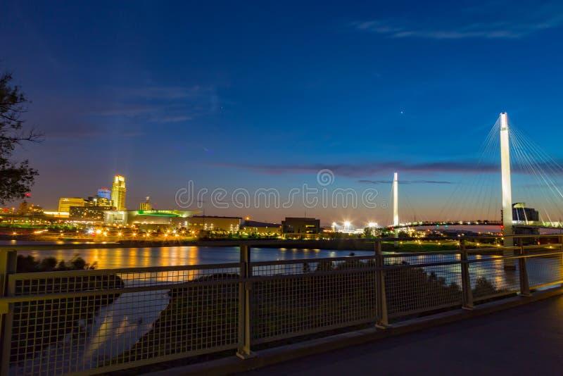 Im Stadtzentrum gelegenes Omaha nachts mit der Kerry-Fußbrücke, wie von der Brücke gesehen stockfotografie