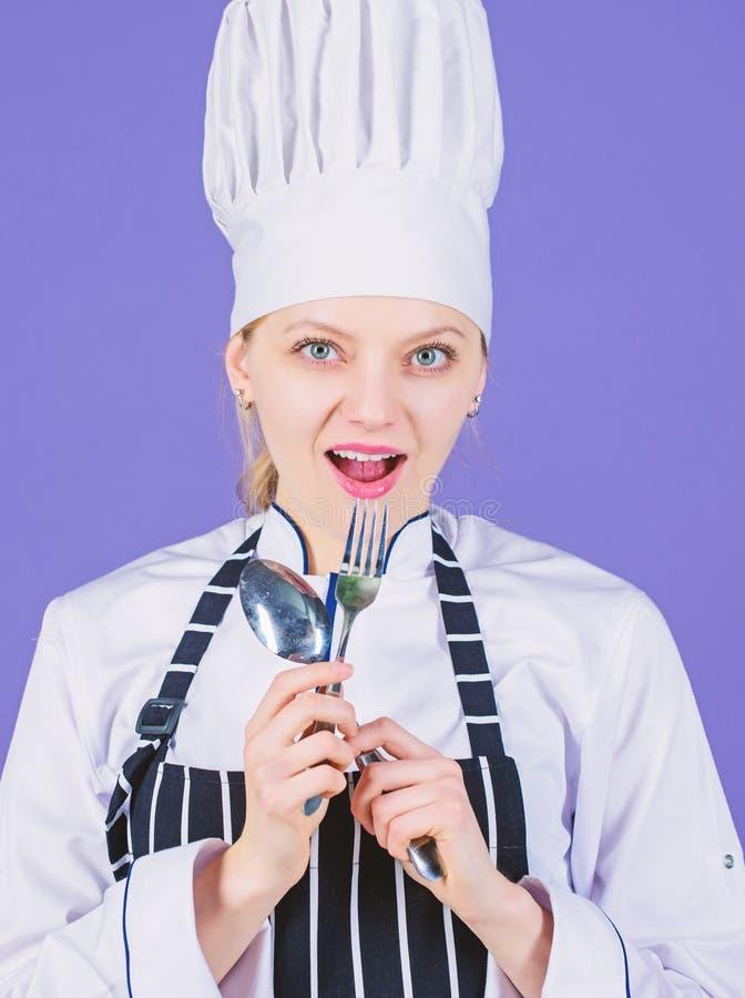 Im un grand cuisinier Cuisini?re sensuelle de dame Joli cuisinier tenant la cuill?re et la fourchette d'acier inoxydable Port de  image libre de droits