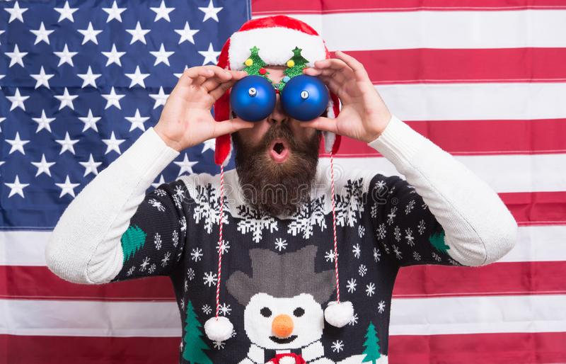 Im watching you. Bearded man look through funny eye glasses. Funny sight. Funny Santa on stars and stripes background royalty free stock photos