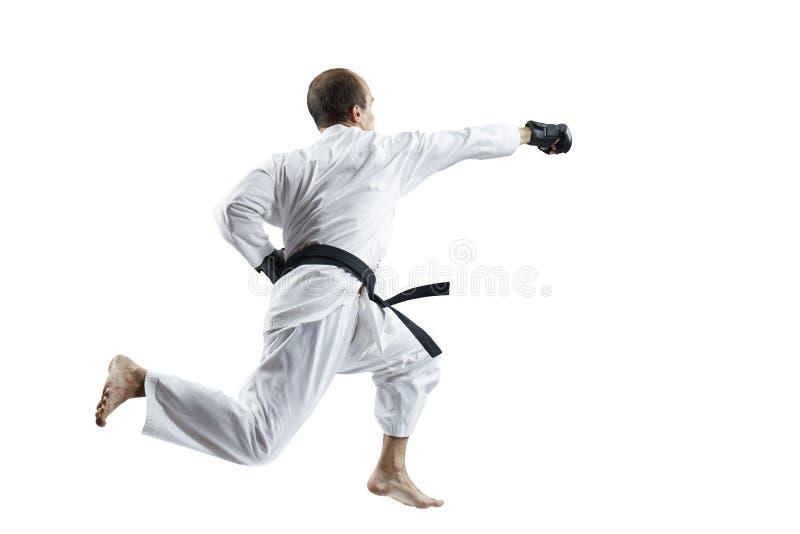 Im weißen karategi und in den schwarzen Handschuhen die Athletenschläge mit einer Hand im Sprung lokalisiert lizenzfreie stockbilder