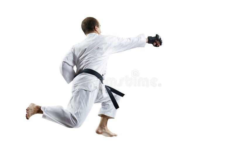 Im weißen karategi und in den schwarzen Handschuhen die Athletenschläge mit einer Hand im Sprung lokalisiert lizenzfreie stockfotos