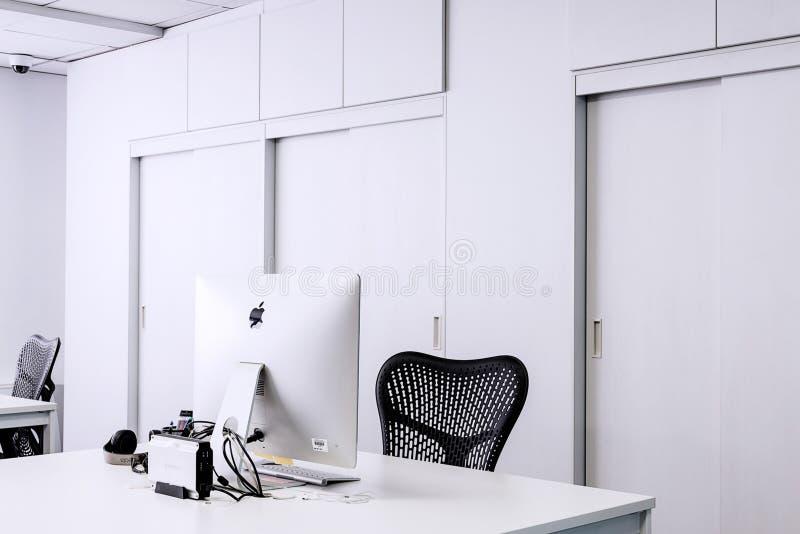 在白色木书桌旁边的黑滤网办公室辗压椅子有白色Imac的 免版税库存图片