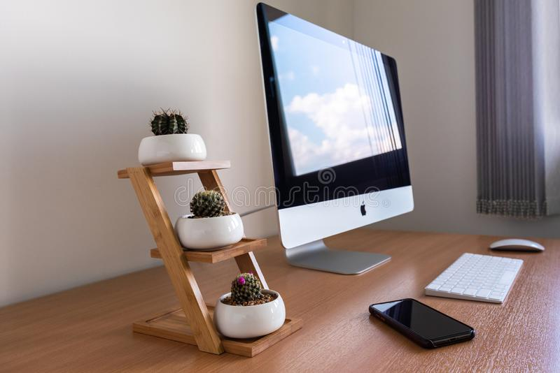 iMac computer, toetsenbord, magische muis, cactuspotten en iPhone X op houten lijst stock afbeeldingen