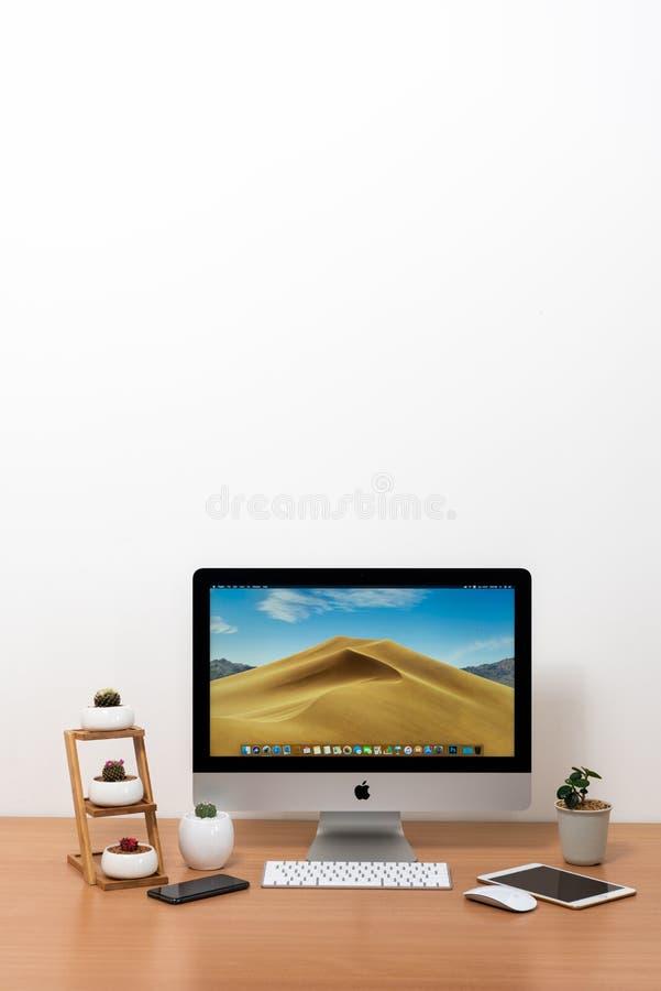 IMaccomputer, toetsenbord, magische muis, iPhone X, iPad mini, installatievaas en cactuspotten op houten lijst royalty-vrije stock foto's