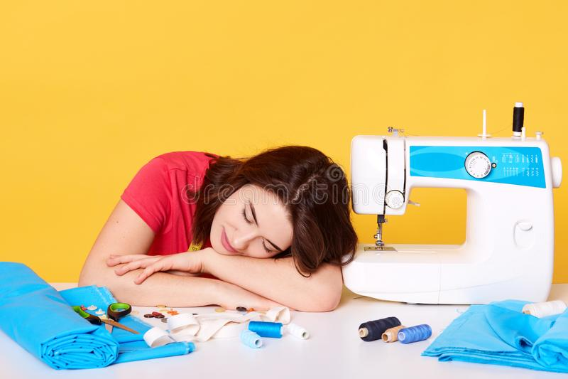 Imagínese de trabajos de la mujer joven como costurera, cansado de ropa de costura y cae dormido en el escritorio del wite cerca  imagenes de archivo