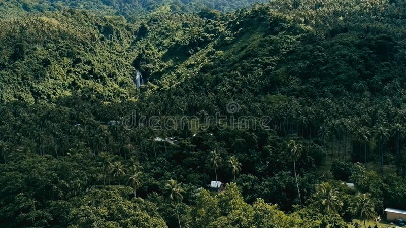 Image aérienne de bourdon d'un village de South Pacific sur une île à distance avec le rivage de plage sablonneuse et la jungle t photo stock