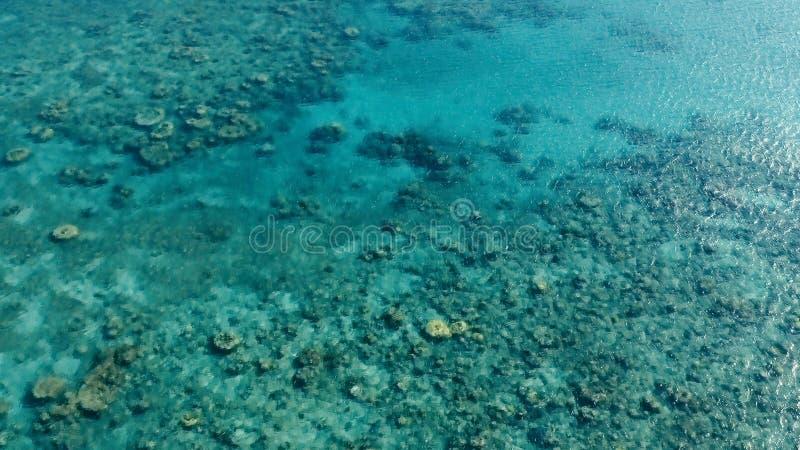 Image aérienne de bourdon de stupéfaction d'un petit bateau de pêche écrivant un ancrage d'océan de mer d'a dans un canal à côté  images stock