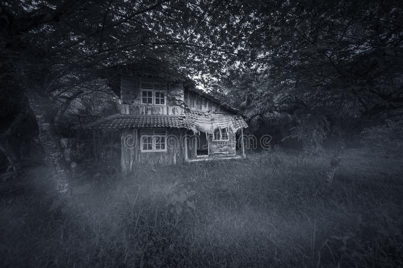 Abandoned wood house looks haunted. Image of abandoned wood house looks haunted with damaged rooftop. Shot at night time royalty free stock images