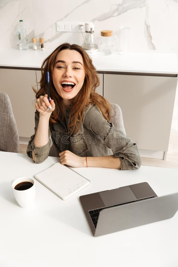 Image from above of smiling woman working in apartment, and using notebook while drinking cup of tea or coffee in morning stock photos