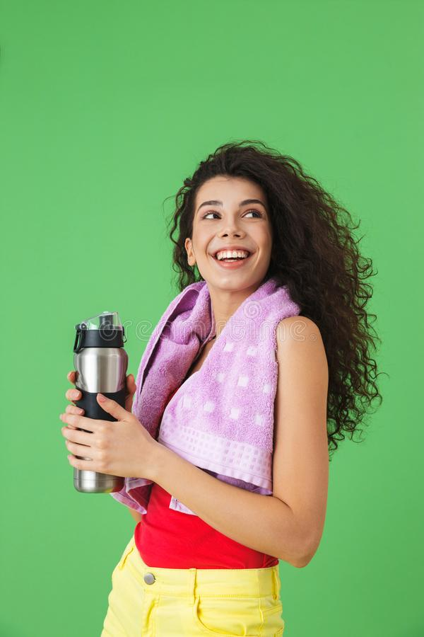 Image of active woman 20s in sportswear rejoicing and drinking water after training royalty free stock photography