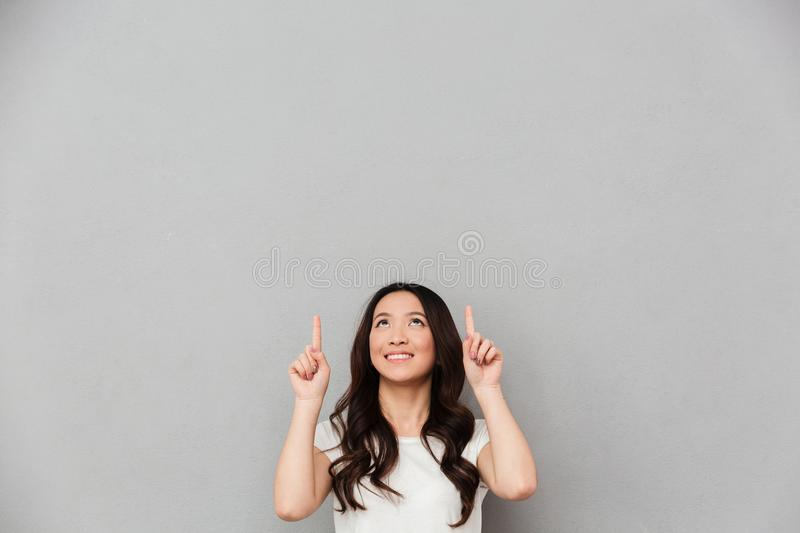 Image of adorable affable woman in casual t-shirt pointing fingers upward on copyspace text or product, isolated over gray. Image of adorable affable woman in stock image