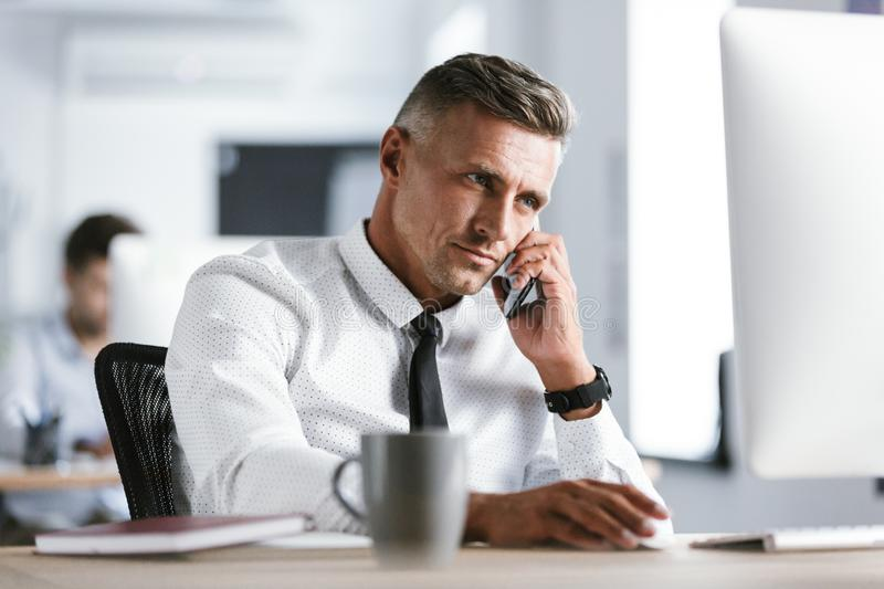 Image of adult businessman 30s wearing white shirt and tie sitting at desk in office by computer, and talking on smartphone royalty free stock images