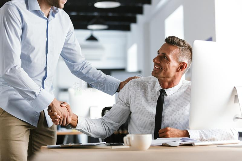 Image of adult businessmen coworkers 30s in formal clothes working in office, and shaking hands together royalty free stock image
