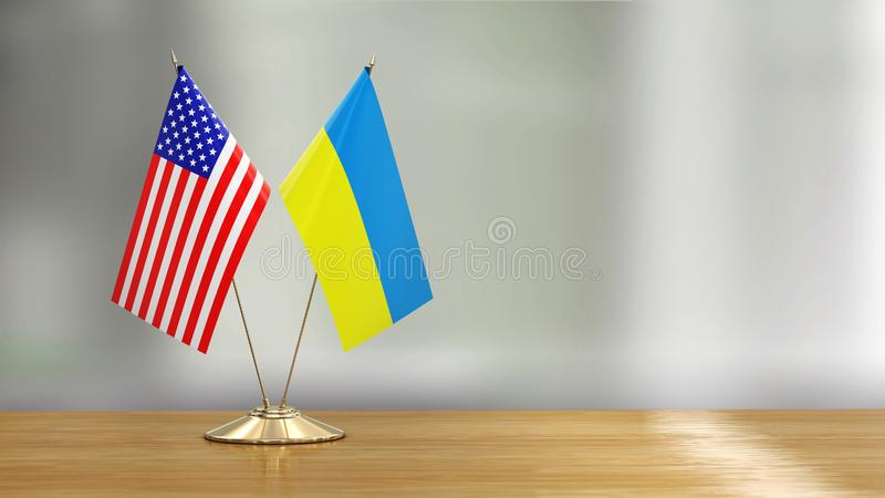 American and Ukrainian flag pair on a desk over defocused background. Image of American and Ukrainian flag pair on a desk over defocused background royalty free illustration