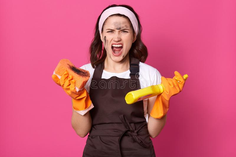 Image of angry tired model posing isolated over pink background in studio, keeps mouth opened, doing household chores, wearing royalty free stock images