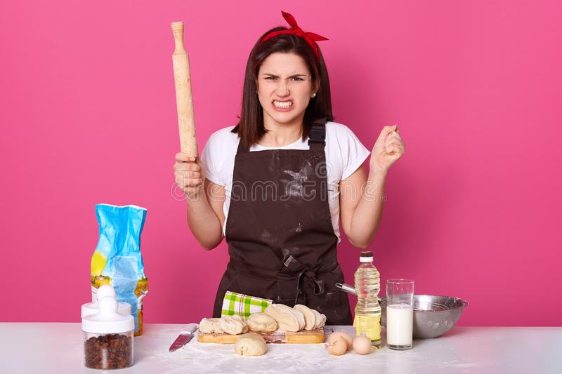 Image of annoyed angry housewife wearing dirty brown apron, white t shirt and red headband, being irritated, having unpleasant royalty free stock photography