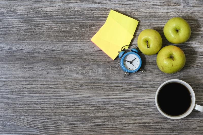 An image of apples, cup of coffee, alarm clock, stickers lying on a wooden table royalty free stock image