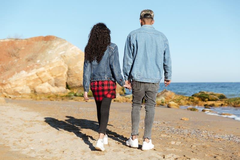 Image arrière de vue des couples affectueux africains marchant dehors photos stock