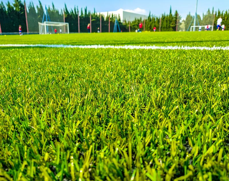 Image of artificial grass in the foreground and background of children playing soccer royalty free stock photography