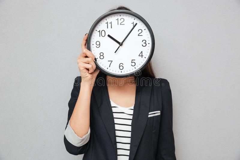 Image of Asian business woman hiding behind a clock. Over gray background royalty free stock photos