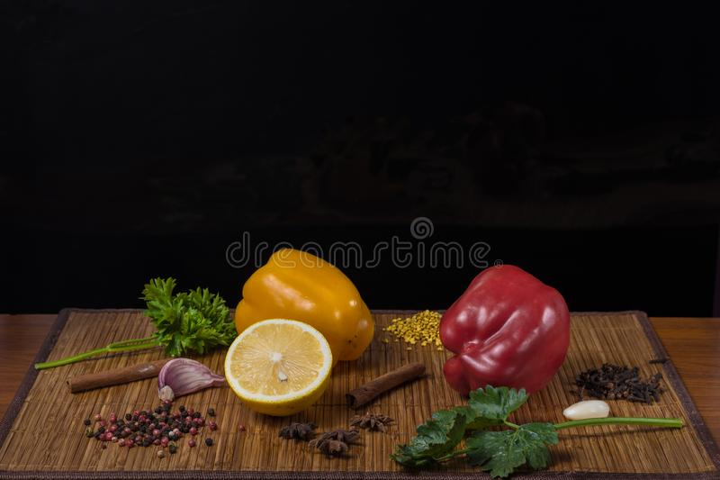 assorted sweet yellow and red peppers with lemon and spices on a black background royalty free stock photo