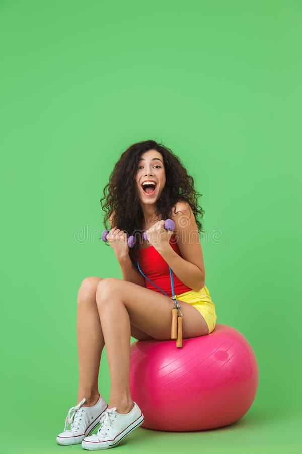 Image of athletic woman 20s wearing summer clothes lifting dumbbells while sitting on fitness ball during aerobics royalty free stock image