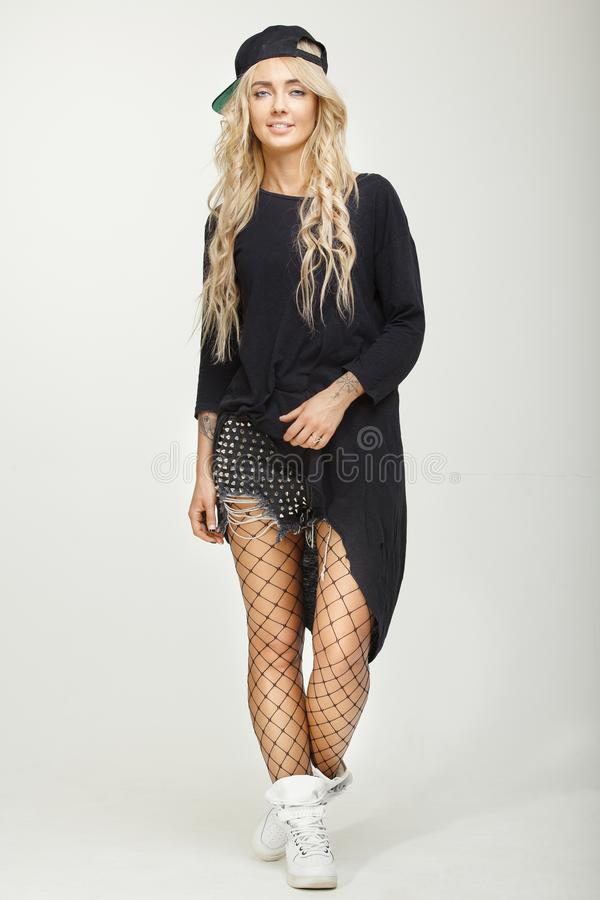 Image of attractive blond girl over white background in stylish swag clothes posing in the studio. Cap, mesh tights stock image