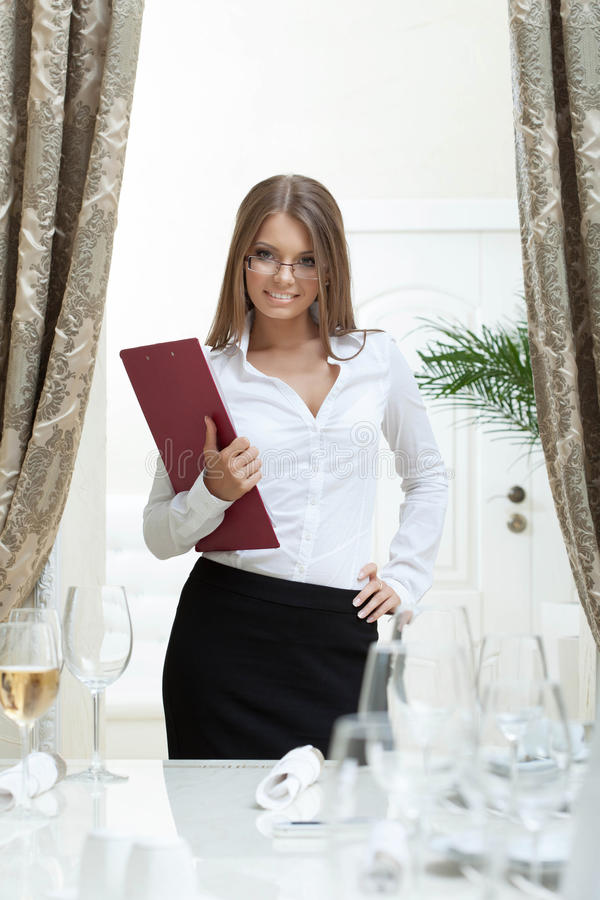 Image of attractive hostess smiling in restaurant royalty free stock photography