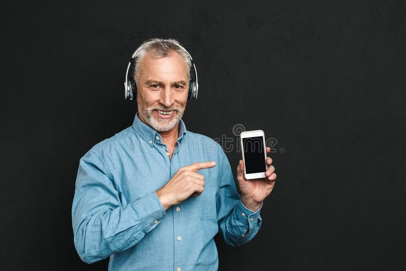 Image of attractive male pensioner 60s with gray hair pointing f stock photos