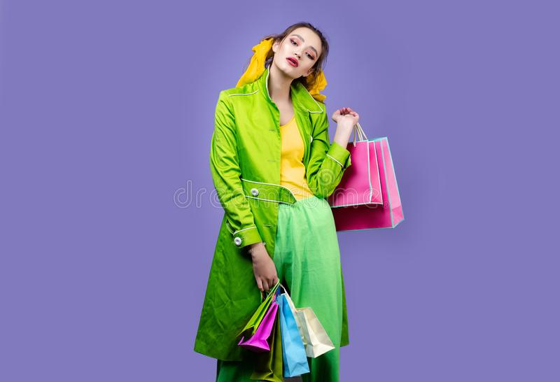 Image of attractive shopper girl dressed in casual clothing, holding paper bags, standing isolated over pyrple royalty free stock images