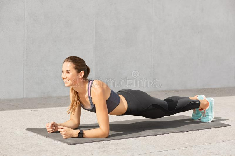 Image of attractive young woman with healthy body, poses on mat in plank pose, does push ups, wants to be in good shape, poses ove stock images
