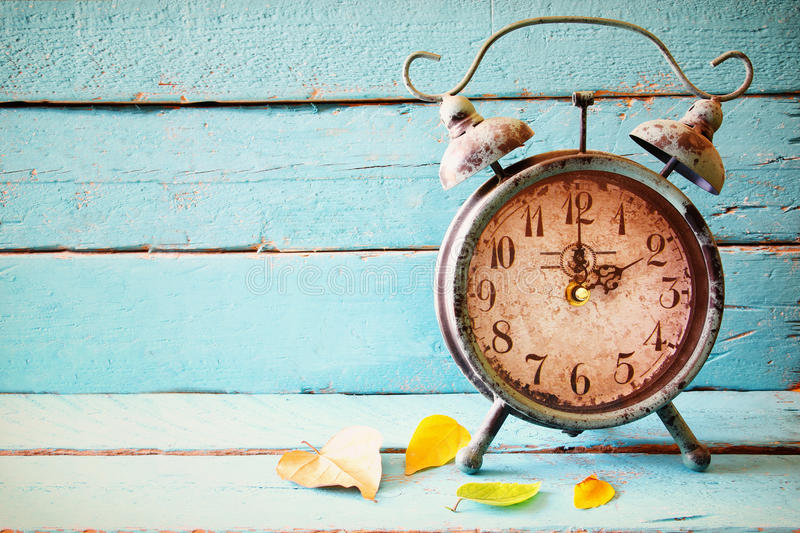 Image of autumn Time Change. Fall back concept. Dry leaves and vintage alarm Clock on a blue rustic wooden background stock photo