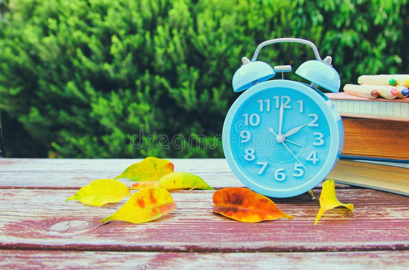 Image of autumn Time Change. Fall back concept. Dry leaves and vintage alarm Clock. On wooden table outdoors at afternoon stock images
