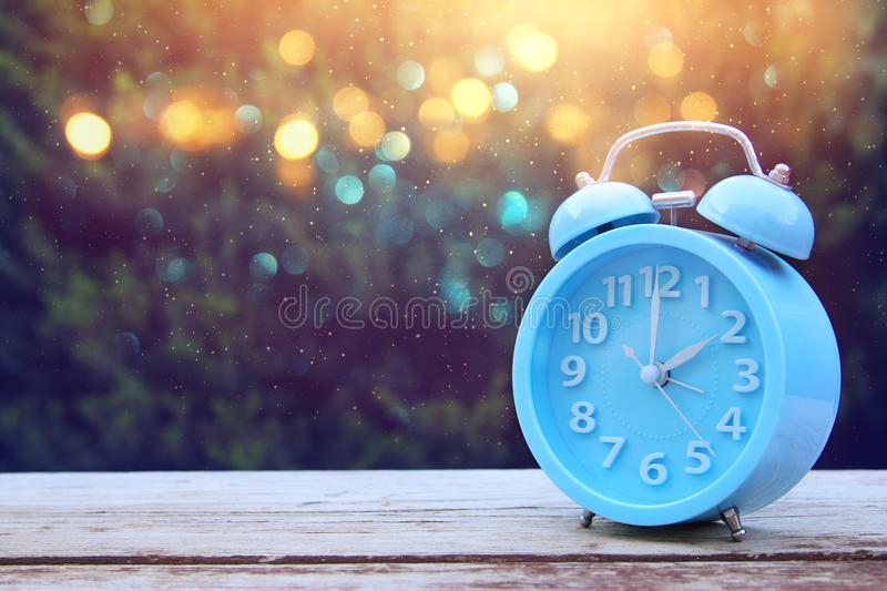 Image of autumn Time Change. Fall back concept. Dry leaves and vintage alarm Clock. On wooden table outdoors at afternoon stock photos