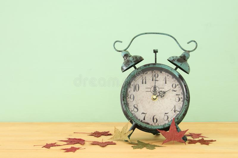 Image of autumn Time Change. Fall back concept. Dry leaves and vintage alarm Clock on rustic wooden table. Image of autumn Time Change. Fall back concept. Dry stock photos