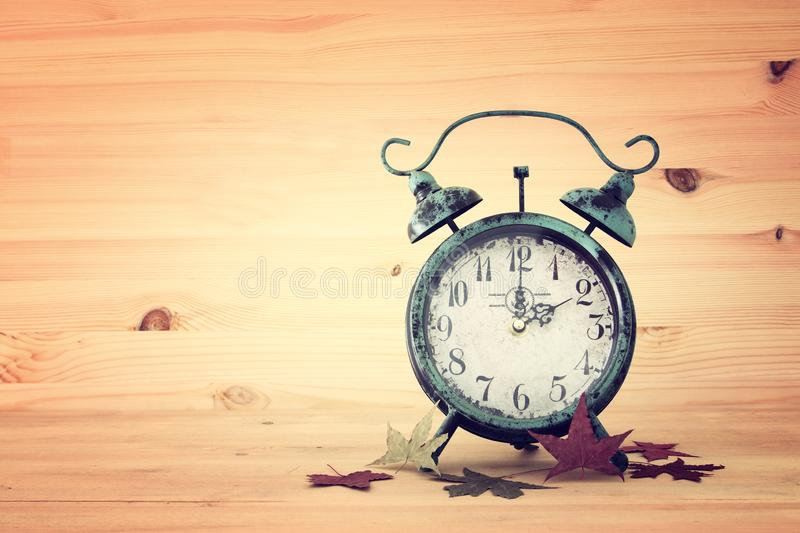Image of autumn Time Change. Fall back concept. Dry leaves and vintage alarm Clock on rustic wooden table. Image of autumn Time Change. Fall back concept. Dry royalty free stock images