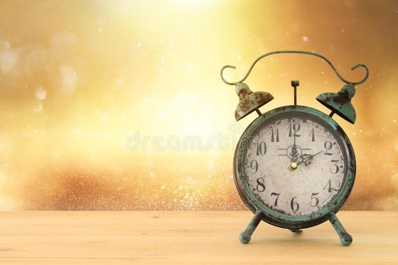 Image of autumn Time Change. Fall back concept. Dry leaves and vintage alarm Clock on rustic wooden table. stock photos