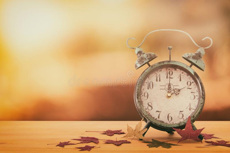 Image of autumn Time Change. Fall back concept. Dry leaves and vintage alarm Clock on rustic wooden table. Image of autumn Time Change. Fall back concept. Dry royalty free stock photo