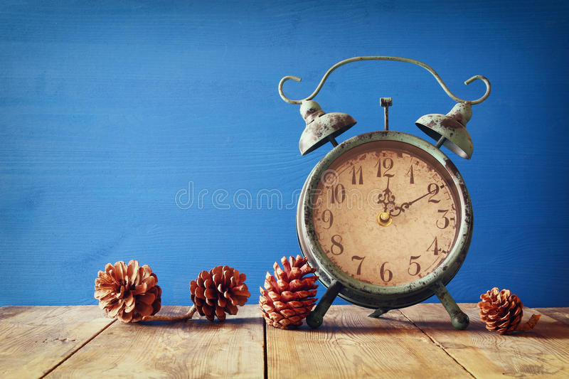 Image of autumn Time Change. Fall back concept. Dry leaves and vintage alarm Clock on rustic wooden table royalty free stock photo