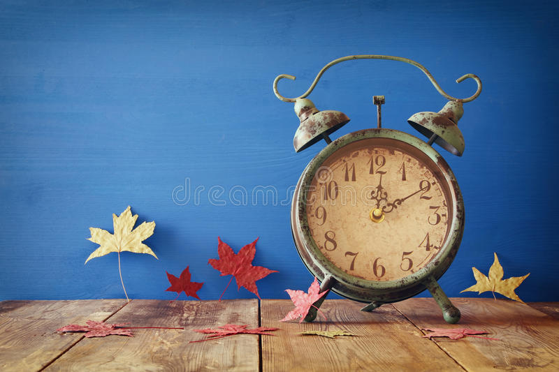 Image of autumn Time Change. Fall back concept. Dry leaves and vintage alarm Clock on rustic wooden table stock photos