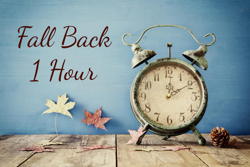 Image of autumn Time Change. Fall back concept. Dry leaves and vintage alarm Clock on rustic wooden table stock images